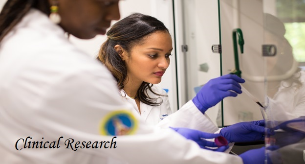 Clinical Research: two women in whitecoats work in a lab